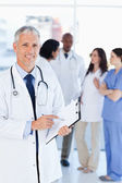 Smiling doctor pointing at a word on his clipboard — Foto Stock