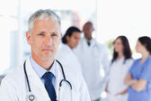Mature doctor looking straight ahead while his team is looking a — Stock Photo