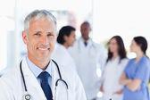 Reife doktor stehen aufrecht während des wartens auf sein team — Stockfoto