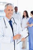 Starší doktor ukazující se zářivým úsměvem, zatímco ukazuje na něco — Stock fotografie