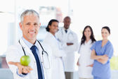 Mature doctor holding an apple while his medical team is looking — Stock Photo