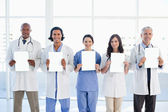 Medical team standing upright in front of the window while showi — Stock Photo