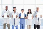Zespół medyczny stojącą przed okna, podczas gdy showi — Zdjęcie stockowe