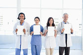 Four medical standing upright while holding blank sheets — Stock Photo