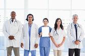 医疗团队站在一名实习生,持有一片空白 — 图库照片