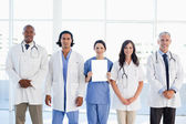 Medical team standing around an intern which is holding a blank — Stock Photo