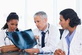Doctor maduro con dos compañeros de trabajo trabajando en una radiografía de los pulmones — Foto de Stock