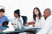 Two smiling medical interns working at the computer near colleag — Stock Photo