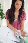 Brunette student taking a calculator — Stock Photo