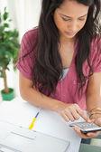Brunette student using a calculator — 图库照片