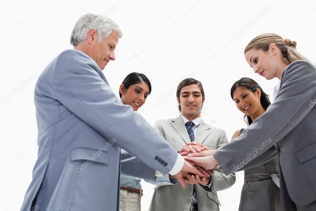 Team putting their hands on each others against white background  Stock Photo #13900870