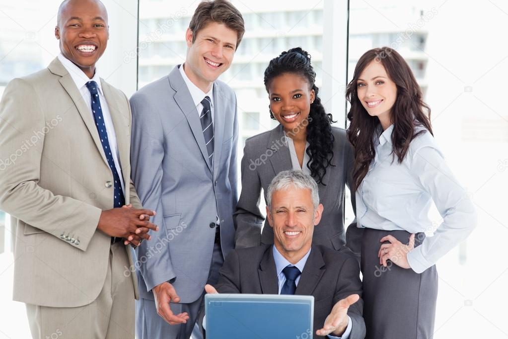Smiling and young business team standing behind their manager and the laptop — Stock Photo #13908919