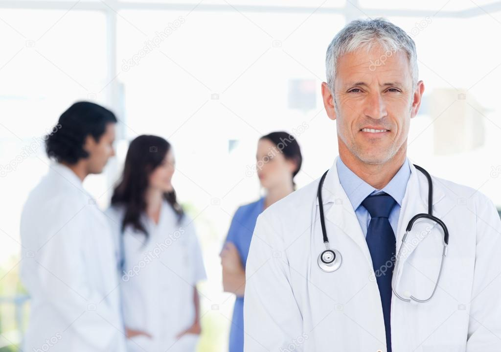 Mature doctor standing upright in front of his interns — Stock Photo #13909509