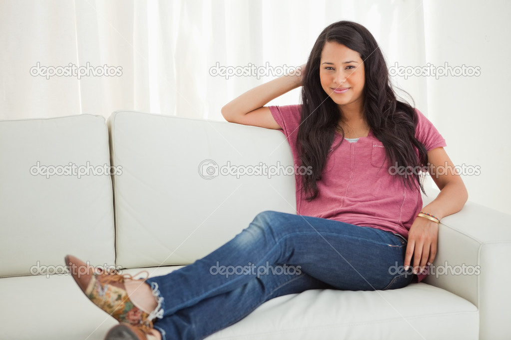 Portrait of a smiling Latino student sitting on a sofa — Stock Photo #13909738