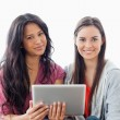 Close up of two women sitting on the couch while looking at the — Stock Photo #13958739