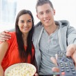 Close up focus shot on the couple sitting on the couch with popc — Stock Photo