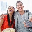 A laughing couple sitting on the couch with popcorn as they watc — Foto de Stock