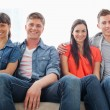 Two couples sit on the couch together looking into the couch — Stock Photo