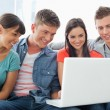 A smiling group of friends sitting around a laptop — Stock Photo