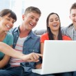 A group of smiling friends gathered around a laptop — Stock Photo
