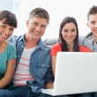 Foto de Stock  : A smiling group of friends sitting together with a laptop as the