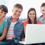 友人としてノート パソコンと一緒に座っているの笑みを浮かべてグループ、 — ストック写真