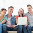 A laughing group sit together on the couch with a laptop watchin — Stockfoto