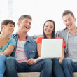 A laughing group sit together on the couch with a laptop watchin — 图库照片