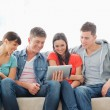 A group of friends sit on the couch while watching a tablet pc — Stock Photo #13958889