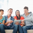 A laughing group of friends watch the tablet pc - Stock Photo