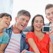 A laughing group pose for a photo in front of them — Stock Photo