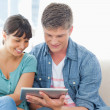 A smiling couple sit on the couch and use a tablet — Foto de Stock