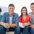 A smiling group sitting on the couch while holding beers — Stock Photo #13959121