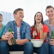 Laughing group of friends sitting with beers in their hands and — Stock Photo #13959128