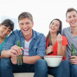Laughing group sit and enjoy beer and some popcorn — Stock Photo