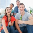 Stock Photo: A laughing group sitting on the couch and the floor with beers i