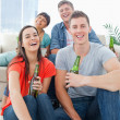 A laughing group sitting on the couch and the floor with beers i — Stock Photo #13959145