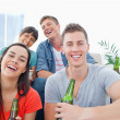 Four in a living room enjoying beer and having fun togeth — Stock Photo
