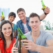 A group of friends celebrating by clinking bottles together — Stock Photo