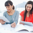 Two girls both using tablet pc's to do their homework — Stock Photo