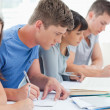 Side view of four students studying and writing together — Foto Stock