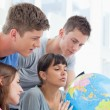 Four students looking at the globe — Foto Stock