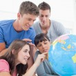 Students pointing to places in the world on a globe — Stok fotoğraf