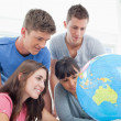 Four students look at the globe together — Stok fotoğraf