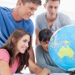 Close up of a group of students looking at the globe — Stock Photo