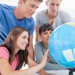 Close up of four looking at the globe of the world — Stock Photo