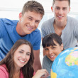 A smiling group of looking into the camera with a globe b — Stock Photo