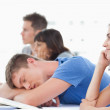 Three students listening in class with another student taking a — Stock Photo