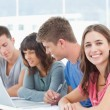 Three students look into the laptop as the fourth student looks — Stock Photo #13959529