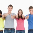 Four standing beside each other give thumbs up — Stock Photo